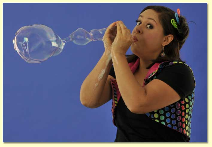 bernadette the Bubble Lady blowing a long soap bubble with her bare hands.