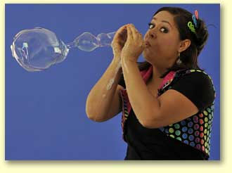 Photograph of the bubble lady blowing an interesting shaped bubble from her hands.