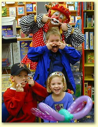 Photo of Maggie the Clown with silly kids making faces.