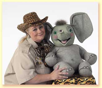 Photo of Margaret Clauder as Masai Maggie, posing with Sneezy The Elephant, a puppet in the show.