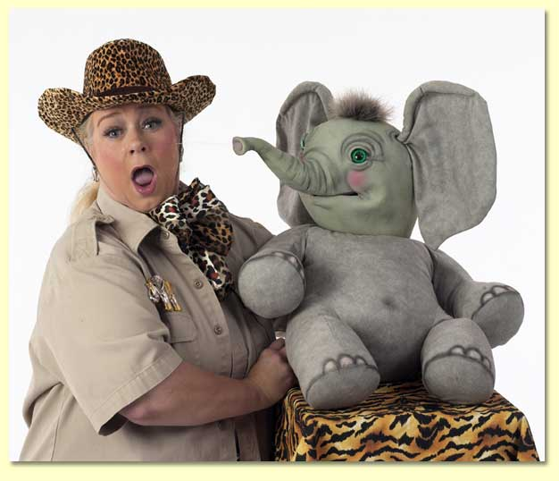 Large photo of Masai Maggie getting squirted by Sneezy the elephant puppet, available for library reading shows in Texas.