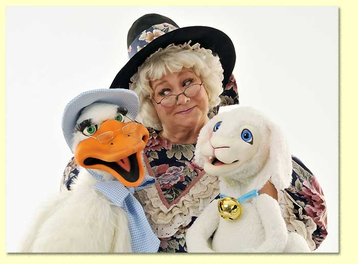 Photograph of the Original Mother Goose, a Texas entertainer, listening to her puppets.
