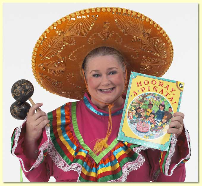 Photograph of Margaret Clauder with musical shakers, in a Mexican dress with the book Hooray A Pinata.