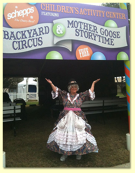 Mother Goose stands at the doorway to the children's Storytime tent, welcoming gusts to enjoy the show.