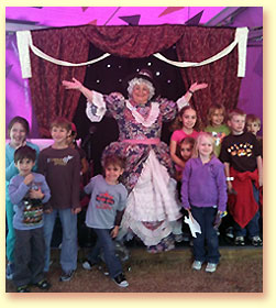 Photograph of Mother Goose with lots of children gathered around her at the State Fair of Texas.