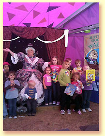 Photograph of Mother Goose with children holding Mother Goose books at the Texas State Fair.